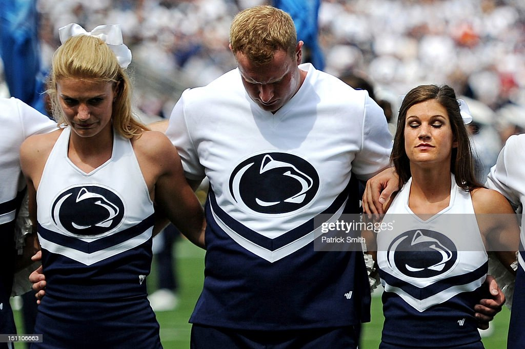 Penn State cheerleaders and fans in the stadium hold a moment of silence for victims of child abuse before the Penn State Nittany Lions and the Ohio Bobcats play in an NCAA football game at Beaver Stadium on September 1, 2012 in State College, Pennsylvania.