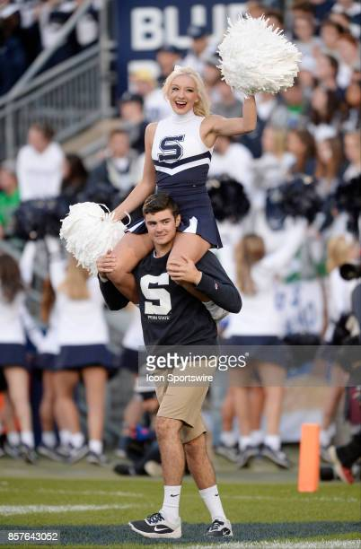 Penn State male and female cheerleader spin around in circles while on shoulders and with pom pom while wearing throwback uniforms and sweaters...