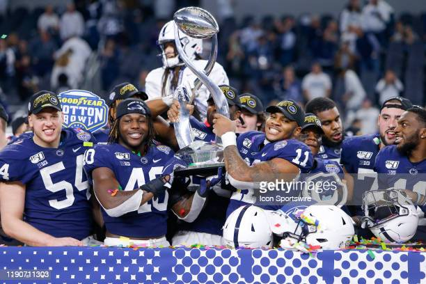 Penn State Nittany Lions linebacker Micah Parsons holds the trophy with his teammates after winning the Cotton Bowl Classic between the Memphis...