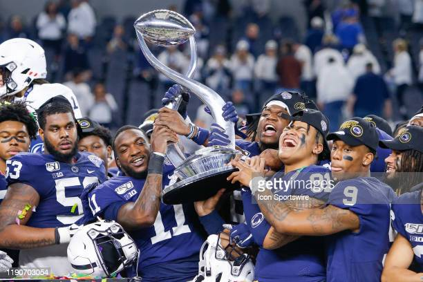 Penn State Nittany Lions wide receiver Daniel George and Penn State Nittany Lions defensive tackle Dvon Ellies hold the trophy with their teammates...