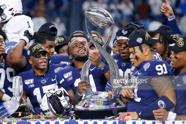 Penn State Nittany Lions wide receiver Daniel George holds the trophy with his teammates after winning the Cotton Bowl Classic between the Memphis...