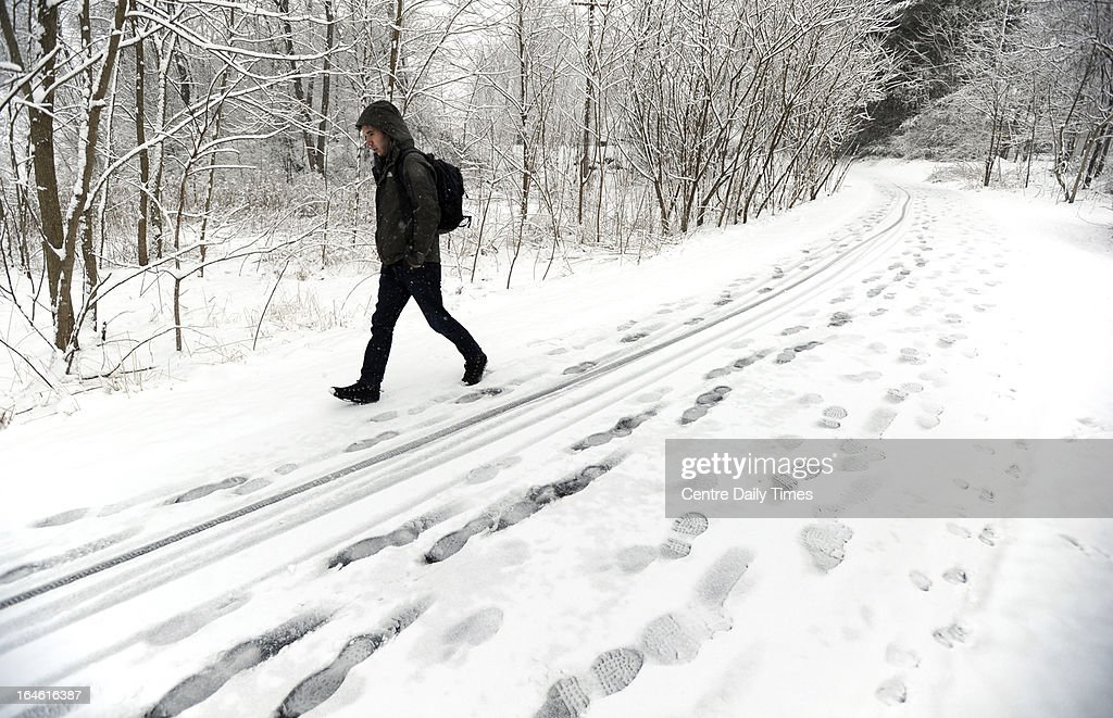Penn State student Andrew Huffard walks along the bicycle path near Sunset Park, in State College, Pennsylvania, on his way to campus. Heavy snow fell throughout Centre County, Monday, March 25, 2013, causing local schools to be closed and hazardous traveling conditions.