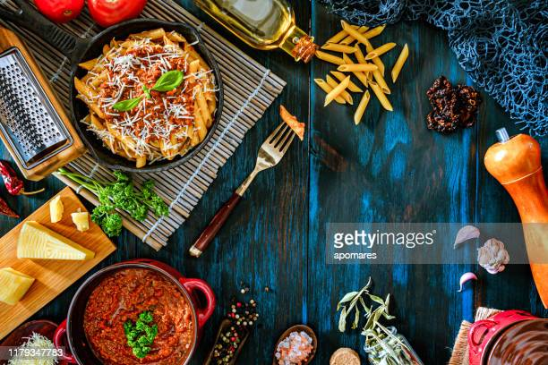 penne with bolognese sauce in serving size casserole with ingredients in rustic pots - bolognese sauce stock pictures, royalty-free photos & images