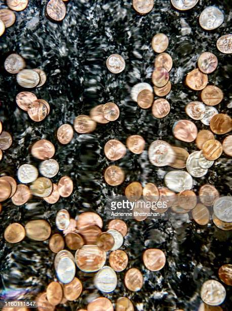 pennies and dimes at the bottom of a coin fountain - fountain stock pictures, royalty-free photos & images