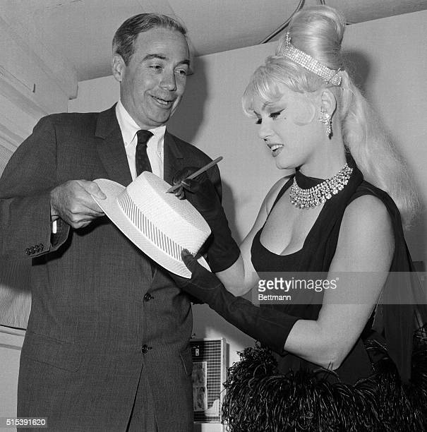 Pennsylvania Governor William Scranton casts an admiring glance as Hollywood starlet Mamie Van Doren autographs his straw skimmer in her dressing...