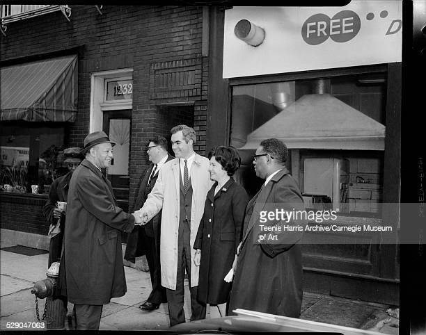 Pennsylvania gubernatorial candidate Robert Casey shaking hands with police officer Karl O Jackson with Tom Forrester in background and Casey's wife...