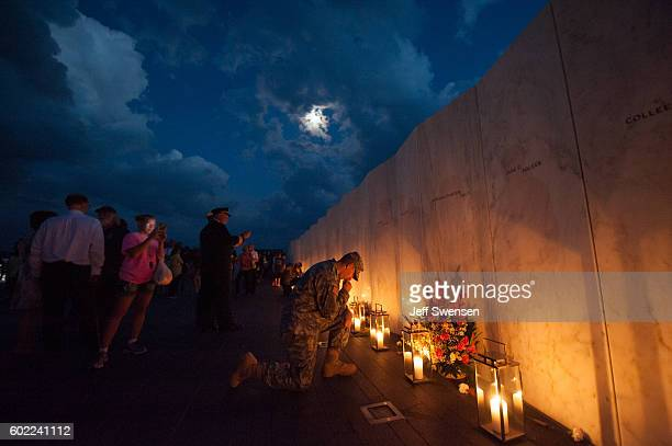 Pennsylvania National Guard Private Edward Noon takes a knee to say a prayer during a luminaria service at the Flight 93 National Memorial on...