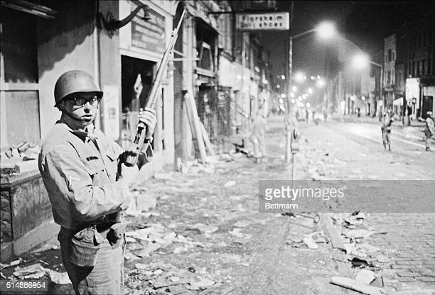 A Pennsylvania National Guardsman patrols a street littered with wreckage from an afternoon of rioting