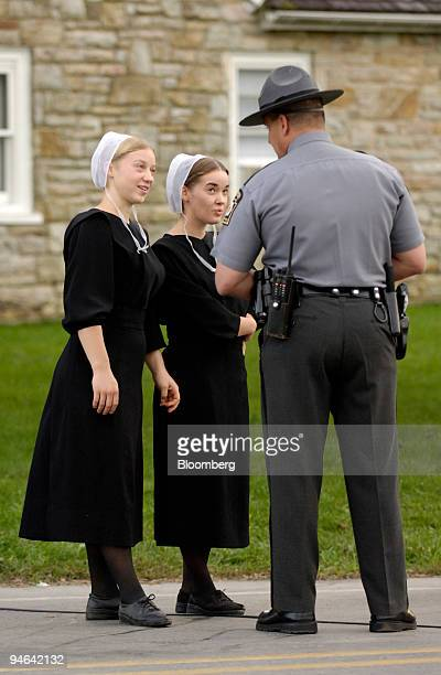 Pennsylvania State Police officer speaks with two women near the scene of a school shooting Tuesday October 3 2006 in Bart Township Pennsylvania A...