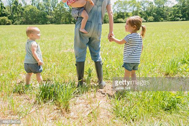 USA, Pennsylvania, Washington Crossing, Mother with three daughters (18-23 months, 2-3) walking on green field