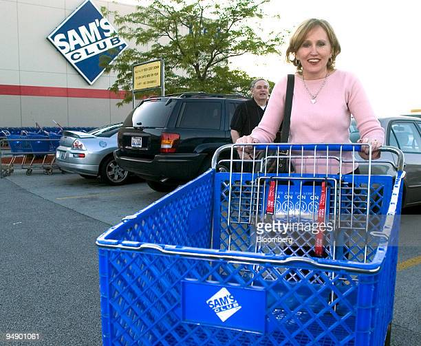 Penny Bates returns her shopping cart as her husband Michael waits by their car after shopping at the Sam's Club store in Tinley Park Illinois on...