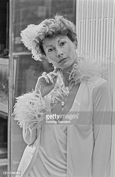 Penny Carter wearing a wrap dress and a 1920s-style hat, UK, 7th August 1974.