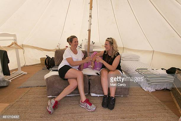 Penny Catchpole and her daughter Emma Catchpole enjoy a drink of champagne inside their bell tent at the PopUp Hotel which offers festival goers...