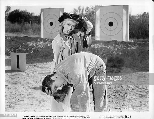 Penny Singleton and Arthur Lake hold onto their heads at a shooting range in a scene from the film 'Blondie's Hero' 1950
