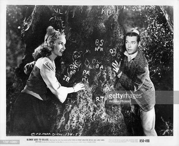 Penny Singleton and Arthur Lake play around tree in a scene from the film 'Blondie Goes To College' 1942