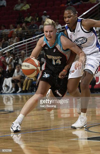 Penny Taylor of the Cleveland Rockers drives around Elaine Powell of the Orlando Miracle in the game on June 8 2002 at TD Waterhouse Centre in...