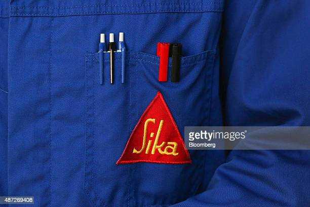 Pens sit above the Sika company logo in an employee's protective coat pocket at a Sika AG adhesives manufacturing facility in Zurich Switzerland on...