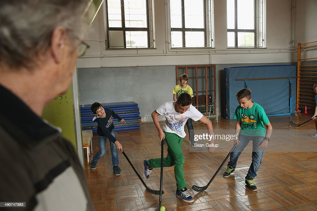 Pensioner and volunteer Heinz Adam oversees 6th grade boys playing floor hockey during a break at the Middle School on May 14, 2014 in Seifhennersdorf, Germany. The state of Saxony officially closed the Seifhennersdorf Middle School in 2012 after only 38 students registered, two short of the 40 the state required to keep the school open. Rather than agree to the school's closing, a group of parents and other volunteers have since assumed the duties of teachers and staff themselves and are trying to get recognition of their 'illegal' school through a court case that now lies with Germany's Federal Constitutional Court. Eleven 6th graders attend the school, even though the state does not recognize their enrollment. School closings across Germany have reached epidemic proportions with 6,100 closures between 2003 and 2013, due in large part to Germany's low birth rate, a phenomenon typical across much of Europe. In Saxony the low birth rate has combined with a steady migration of young people to big cities and to western Germany and the number of schoolchildren has fallen by close to 50% and led to the closure of 1,000 out of a total of 2,500 state schools since 1989.