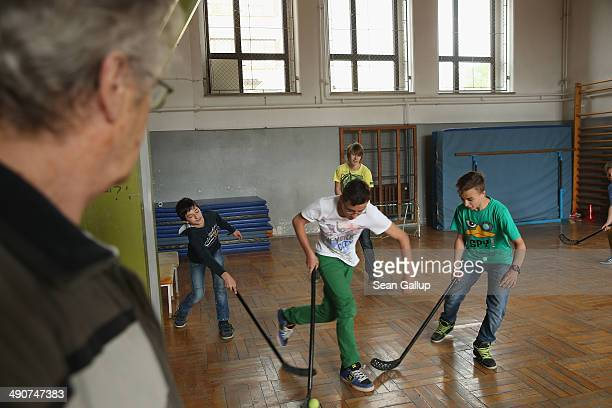 Pensioner and volunteer Heinz Adam oversees 6th grade boys playing floor hockey during a break at the Middle School on May 14 2014 in Seifhennersdorf...