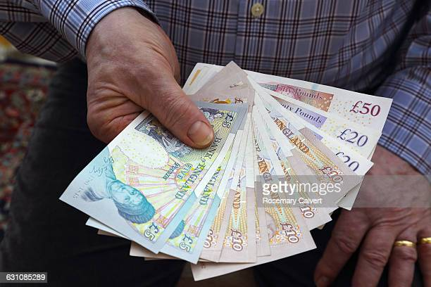 pensioner holding british bank notes in right hand - british pound sterling note stock pictures, royalty-free photos & images