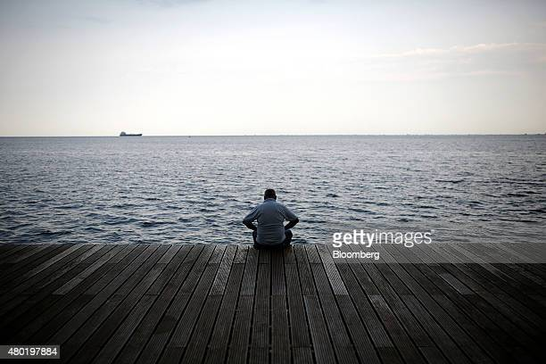 A pensioner looks towards the Aegean Sea as he sits on the seafront in Thessaloniki Greece on Friday July 10 2015 After four months of escalating...