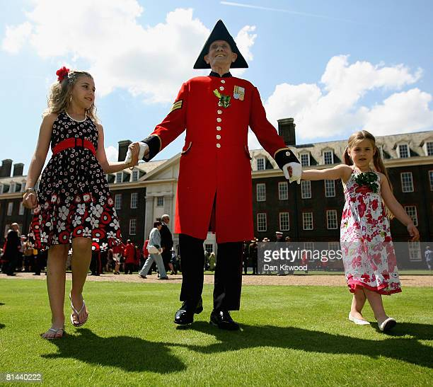 Pensioner Seargent Faulkner walks with his grandchildren Maddison Horne 6, and Stephanie 12, at the Founders Day Parade at Chelsea Royal Hospital on...