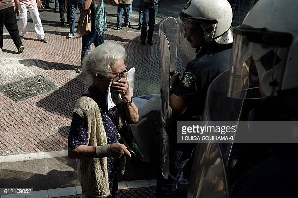 TOPSHOT A pensioner stands in front of riot police after they have used pepper spray during a demonstration in Athens on October 3 2016 Greek police...