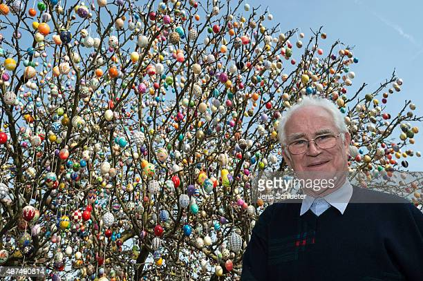 Pensioner Volker Kraft stands next to an apple tree decorated with approximately 10000 Easter eggs on the property of pensioner Volker Kraft on March...