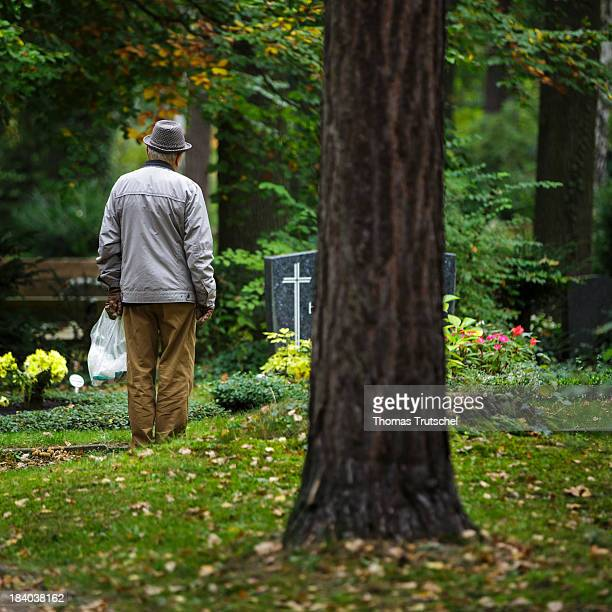 Pensioner widower standing alone and grieving in front of a grave in a graveyard