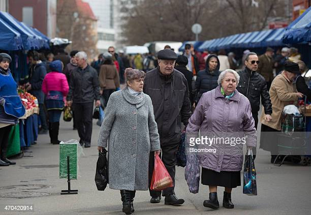 Pensioners carry their purchases as they pass stalls at an open air street market in Moscow Russia on Saturday April 18 2015 Russia will extend a...