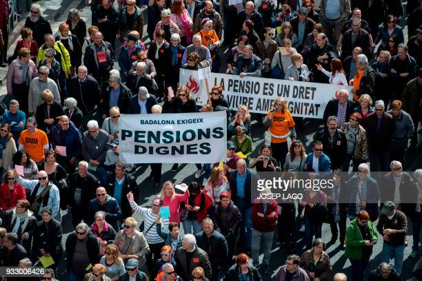Pensioners hold up banners as they march in Barcelona on March 17 during a protest called by 'Marea Pensionista' and supported by the main Spanish...