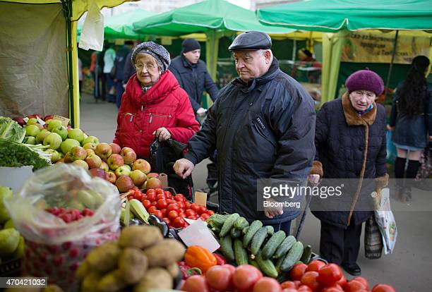 Pensioners look at a fresh fruit and vegetable stall at an open air street market in Moscow Russia on Saturday April 18 2015 Russia will extend a...