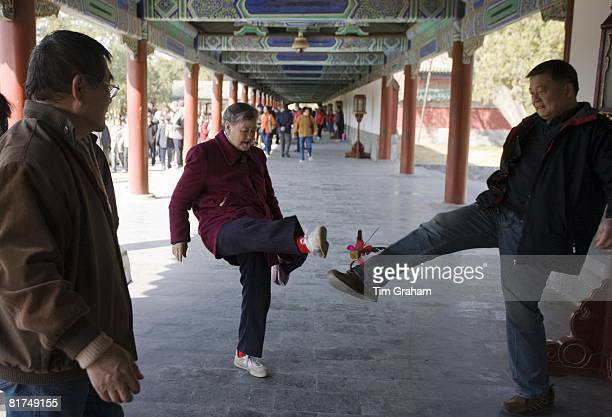 Pensioners play shuttlecock with their feet in the Ghost Corridor in park of the Temple of Heaven Beijing China