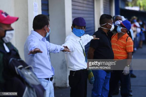 Pensioners queue outside a bank wearing face masks as a preventive measure against the spread of the COVID-19 coronaavirus in San Salvador, on March...