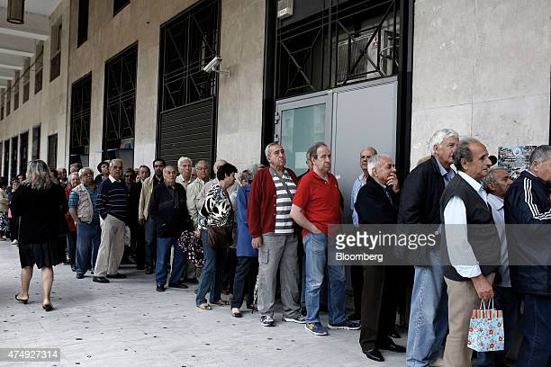 Pensioners queue outside a National Bank of Greece SA bank branch before collecting their pension payments in Thessaloniki Greece on Thursday May 28...