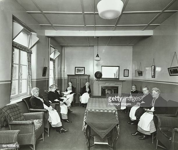 Pensioners sitting and reading in the Women's Day Room at the Lambeth Home for Aged Poor London 1935 Women sit in armchairs ranged round the walls
