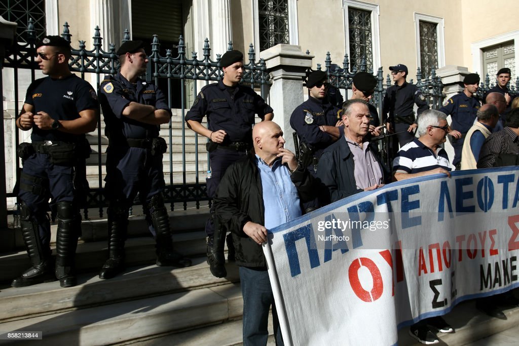 Pensioners stand in front riot police officers during a rally against new pension cuts, outside the Counsel of State, the Supreme Administrative Court of Greece, in Athes on October 6, 2017