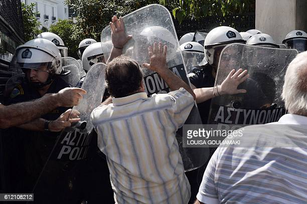 TOPSHOT Pensioners try to pass police blockade to go towards the Greek PM's office during their demonstration in Athens on October 3 2016 Greek...