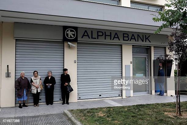 Pensioners wait outside a closed Alpha Bank AE bank branch before collecting their pension payments in Thessaloniki Greece on Thursday May 28 2015...