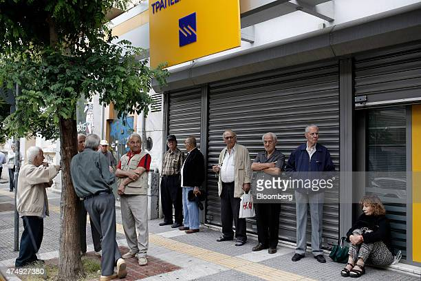 Pensioners wait outside a closed Piraeus Bank SA bank branch before collecting their pension payments in Thessaloniki Greece on Thursday May 28 2015...