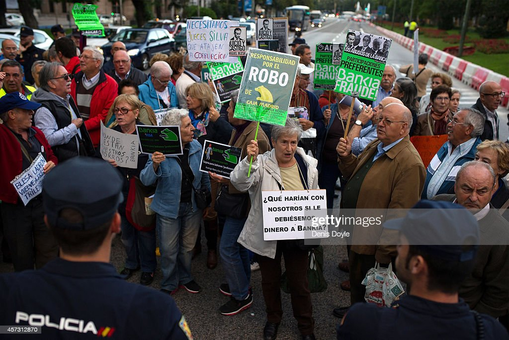 Pensioners who lost money investing in preferential shares of rescued bank Bankia briefly block traffic near Madrid's High Court where Rodrigo Rato, former chairman of rescued bank Bankia and former head of the International Monetary Fund is scheduled to answer allegations of misusing company credit cards on October 16, 2014 in Madrid Spain. Judge Fernando Andreu is questioning Rato along with former Bankia chief Miguel Blesa and former financial director Ildefonso Sanchez Barcoj.