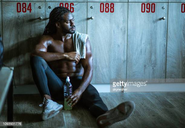 pensive african american athlete resting at gym's locker room. - riposarsi foto e immagini stock