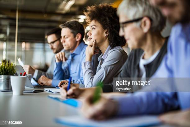 pensive african american businesswoman among her colleagues in the office. - in a row stock pictures, royalty-free photos & images
