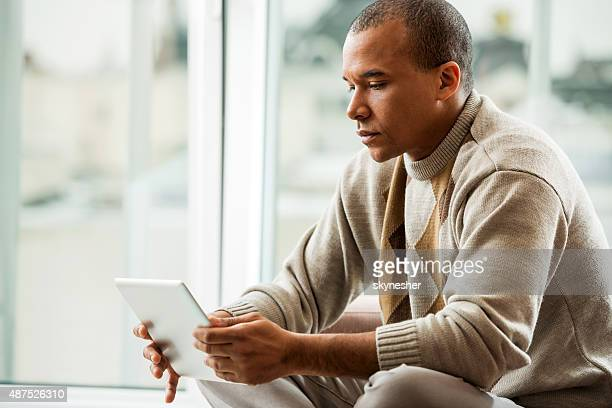 Pensive African American using touchpad.