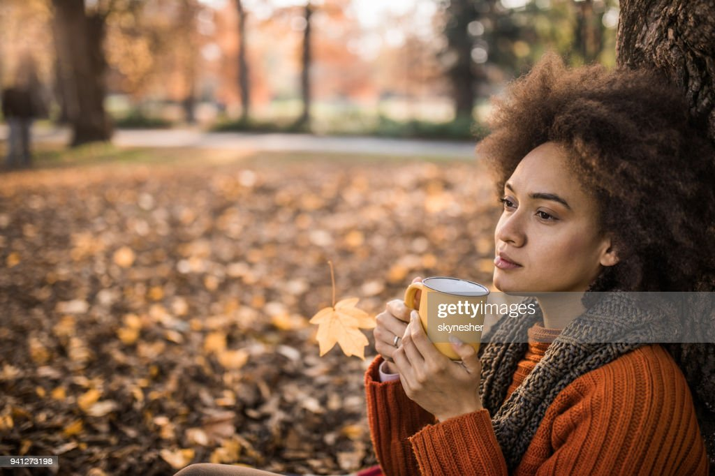 Pensive African American woman drinking tea during autumn day in nature. : Stock Photo
