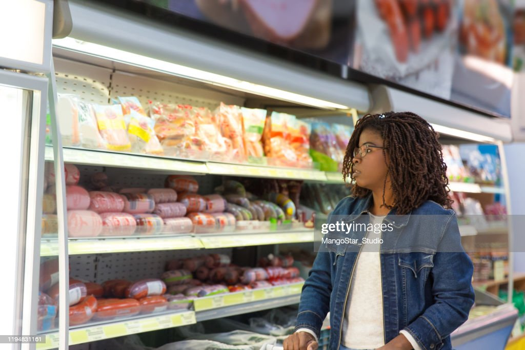 Pensive African American woman wheeling shopping cart : Stock Photo