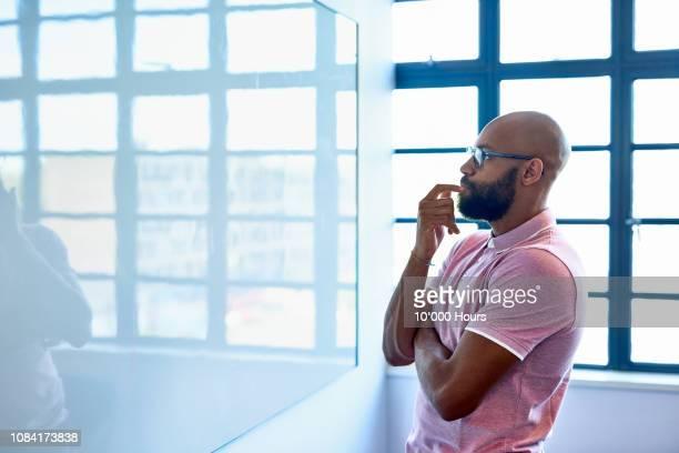 pensive african entrepreneur staring at blank whiteboard in office - thinking outside the box englische redewendung stock-fotos und bilder