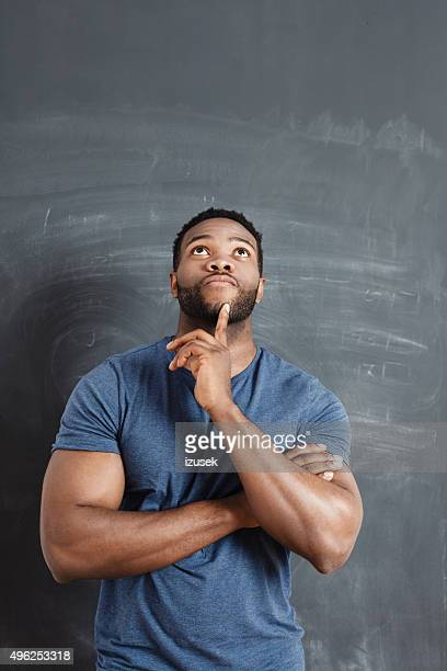 pensive afro american man against blackboard - black male bodybuilders stock photos and pictures