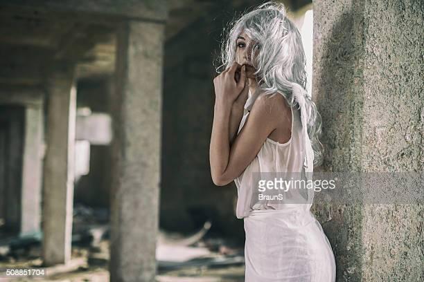 Pensive angel in a ruin looking away.