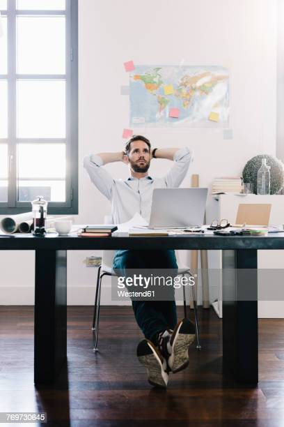 Pensive architect sitting at desk in his office
